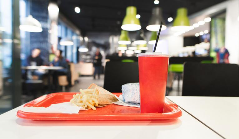 Red tray with Fast Food menu is on the table in the restaurant.