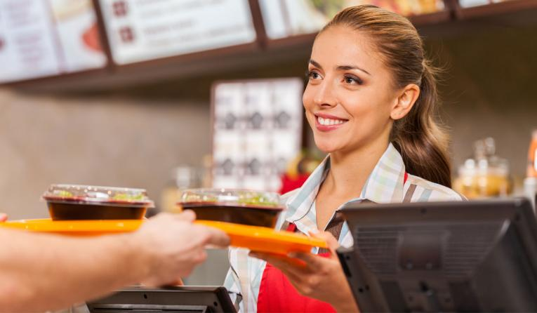 Restaurant worker hands food to a customer.