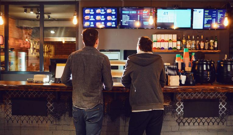 Two men order food at a fast-food restaurant.