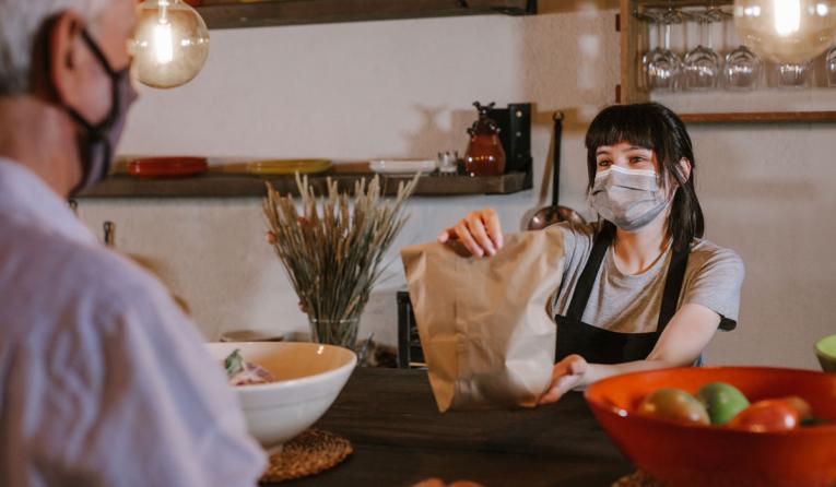 Waitress wearing protective face mask giving bag to customer in a restaurant.