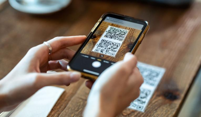 Woman using smart phone to scan the QR code to select food menu in the restaurant.