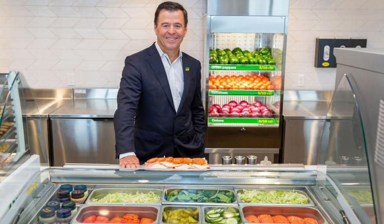 Subway CEO John Chidsey poses behind the sandwich counter.