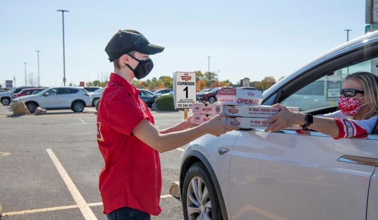 Toppers Pizza employee handing food to employee.