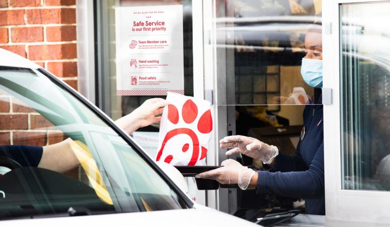 Chick-fil-A employee handing food out the window of a drive-thru.