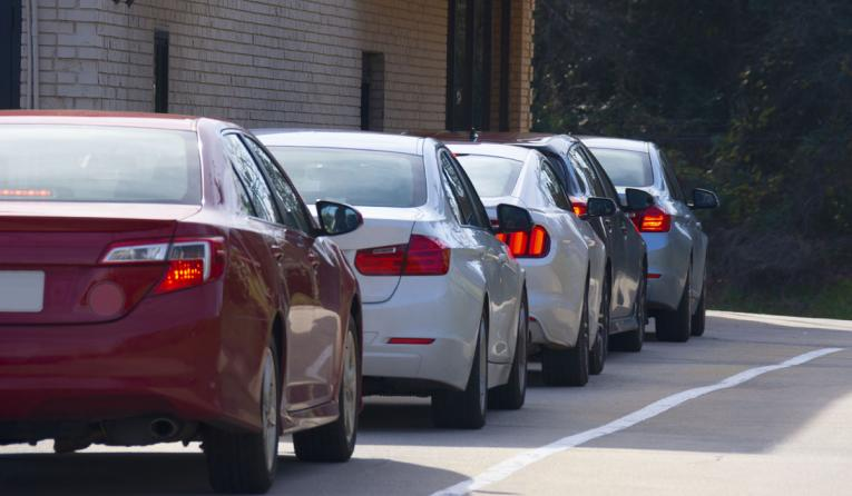 Cars in line at a drive-thru.