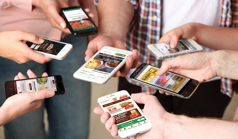 Hand holding phones with various restaurant ordering menus on screens