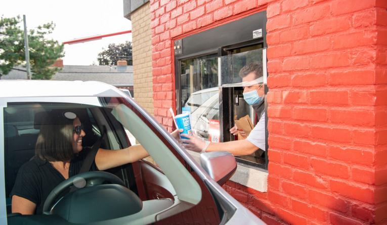 Wendy's drive-thru employee handing food to a customer.