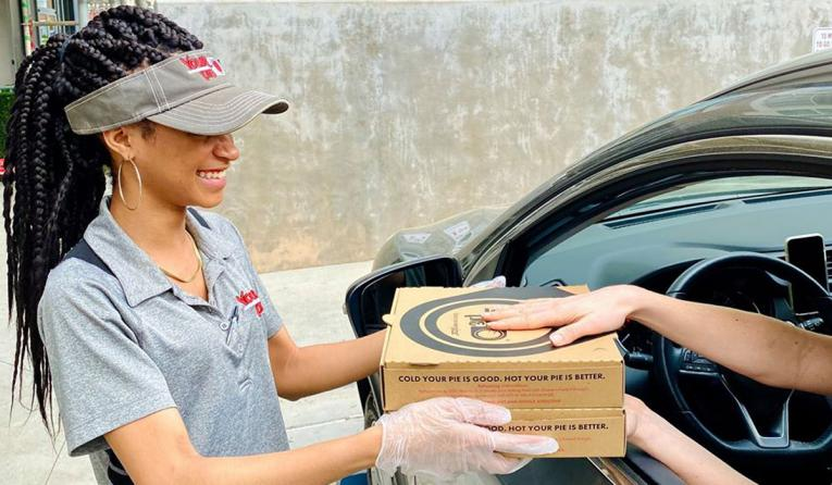 Your Pie employee handing food to someone in their car.