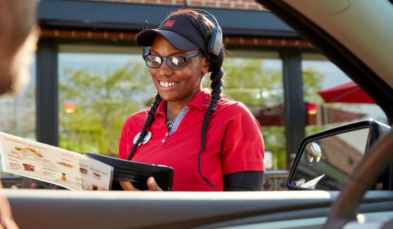 A Chick-fil-A worker takes an order at the car in the drive thru.