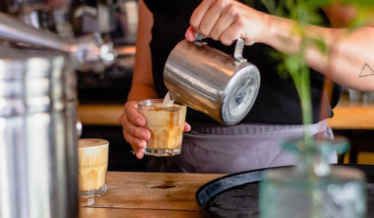 A barista pours a cup of coffee.
