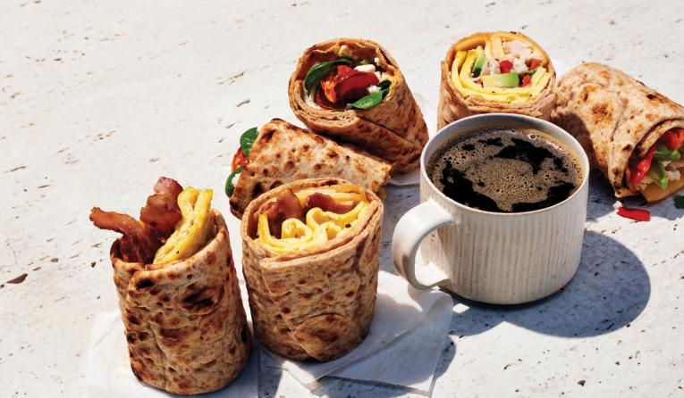 Coffee and wraps on a table from Panera Bread.