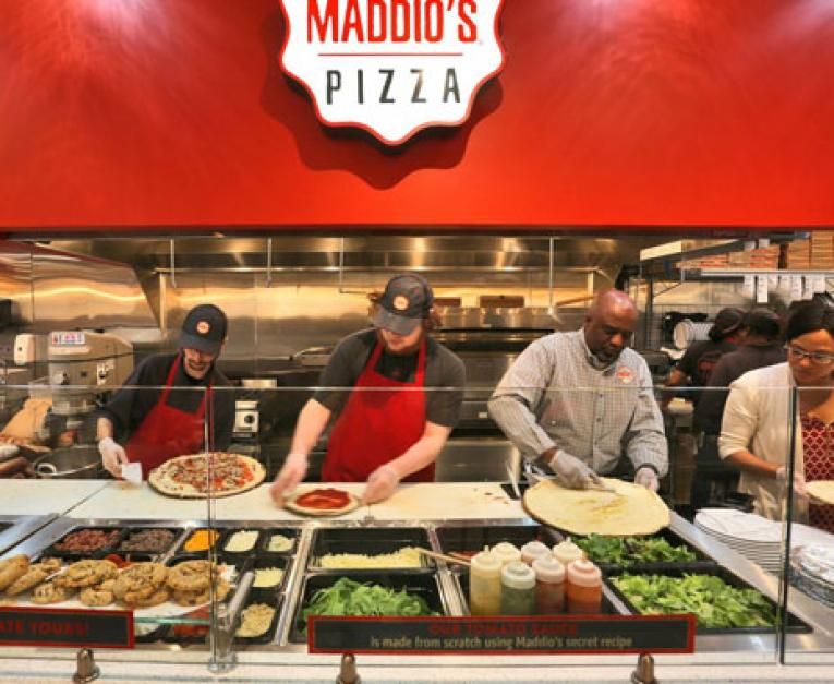 Employees prepare pizza at Uncle Maddio's new service line in Georgia, showcasing the restaurant chain's fresh design and commitment to the customer experience.