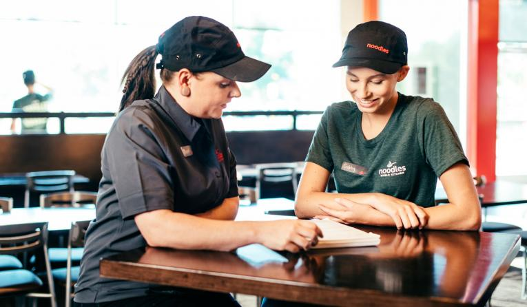 A Noodles & Company manager talks with an employee.