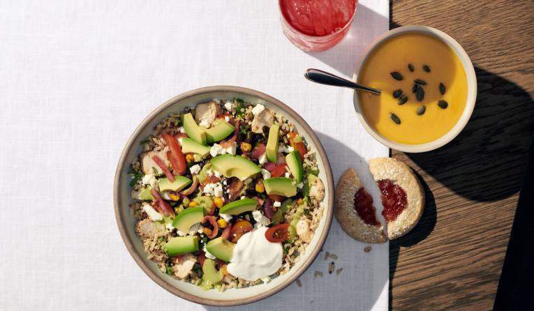 Panera Bread's Baja Grain Bowl on a table next to soup.