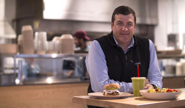 CEO Chris Fuqua stands at a table with food at B.GOOD.