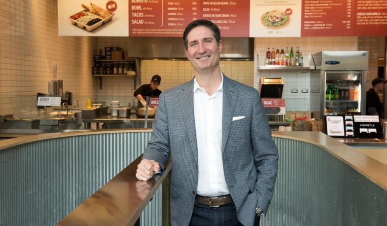 Chipotle CEO Brian Niccol poses in a restaurant.
