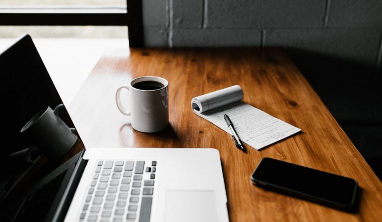 MacBook Pro, white ceramic mug, and black smartphone on table.