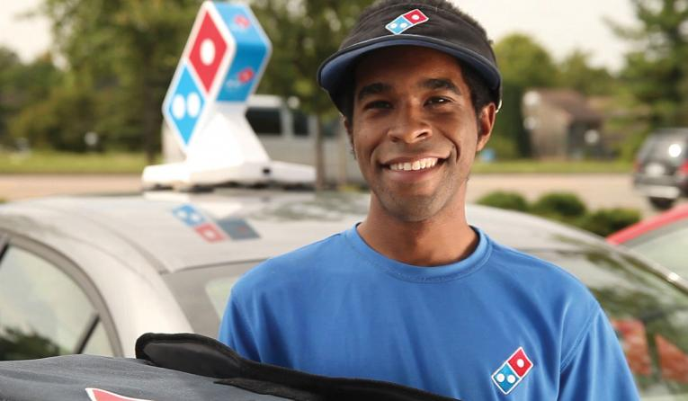 A Domino's delivery driver holds a pizza.