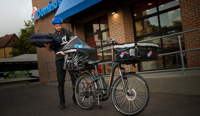 Domino's delivery driver stands near an e-bike.