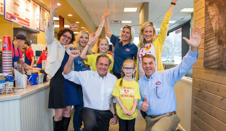 Jersey Mike's founder & CEO Peter Cancro (kneeling, left) celebrates the company's 8th Annual Day of Giving with Callyn Stanley (front center) and area director Mike Spiegel at the Olathe, Kansas, restaurant.