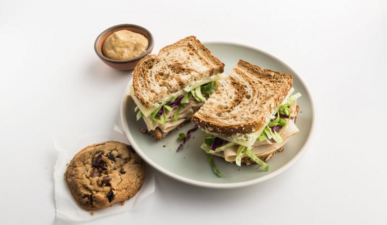 The Grüben: Zoës signature sandwich with sliced turkey, Manchego cheese, crunchy Mediterranean slaw and feta spread layered on marble wheat bread, served with a Zoës chocolate chip cookie.