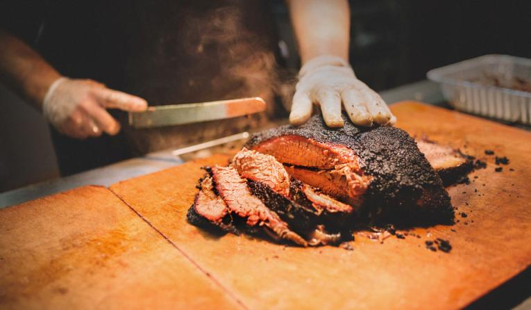 Brisket being sliced on a cutting board at City Barbecue.