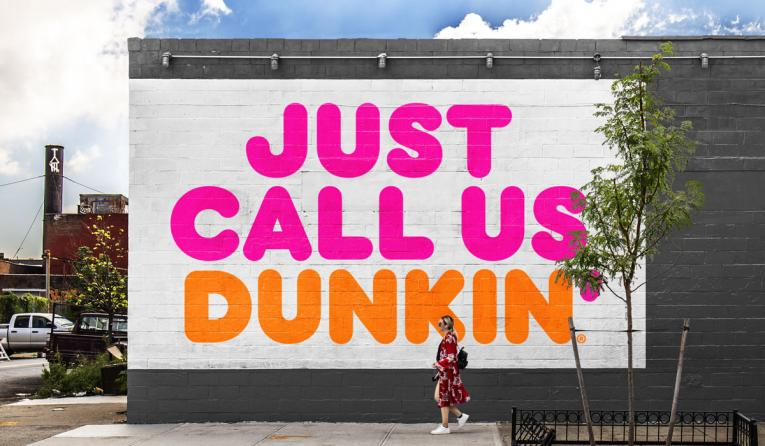A woman walks by a mural that says Just Call Us Dunkin'.