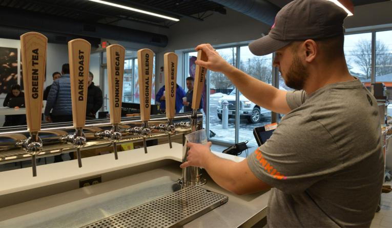 A workes pours nitro cold brew from a tap at Dunkin' Donuts new restaurant deisgn in Massachusetts.