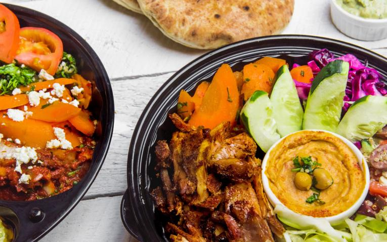 Assorted bowls of food at The Hummus & Pita Co.