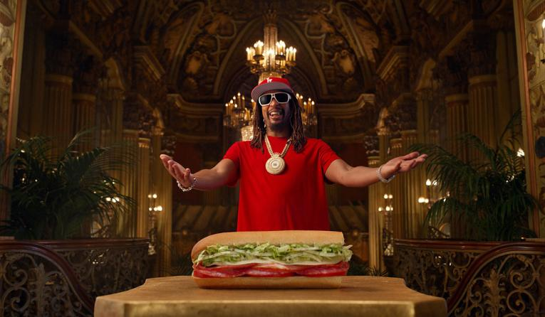Lil Jon posed behind a Jimmy John's sandwich.