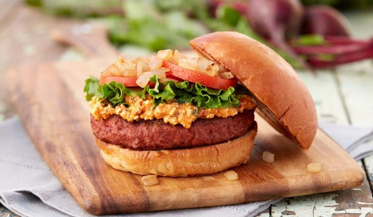 The Beyond Burger is topped with signature spicy feta, lettuce, tomato, chopped onion, and served on a fresh brioche bun.