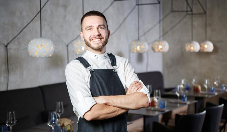 A young, smiling waiter in a restaurant, standing next to the tables with a glass of wine. He wears an apron, looks confidently, folded arms over his chest.