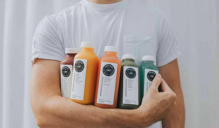 Person holding bottles of Pressed Juicery juices