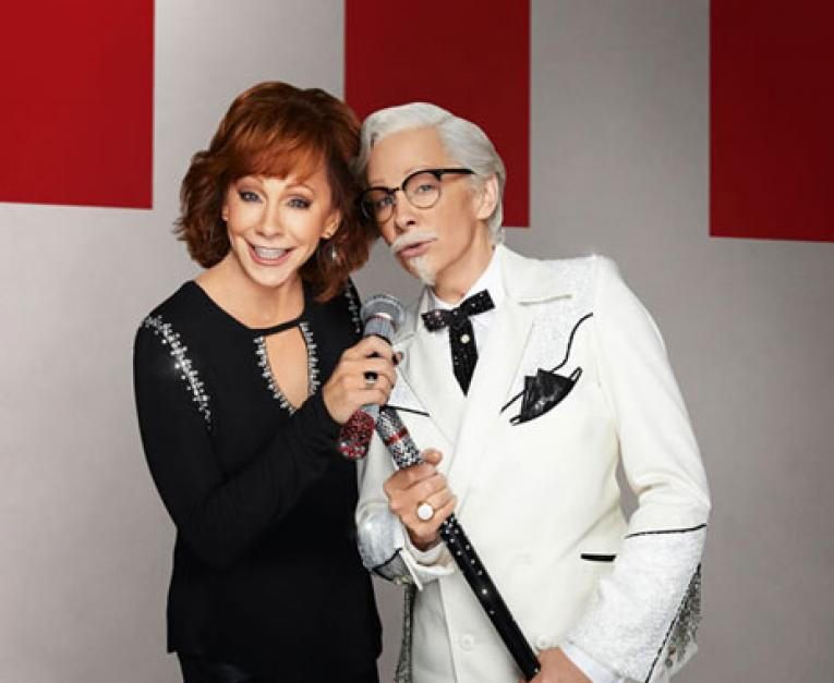 Music star Reba McEntire standing next to herself as Colonel Harland Sanders. She's the first female to play the KFC mascot.
