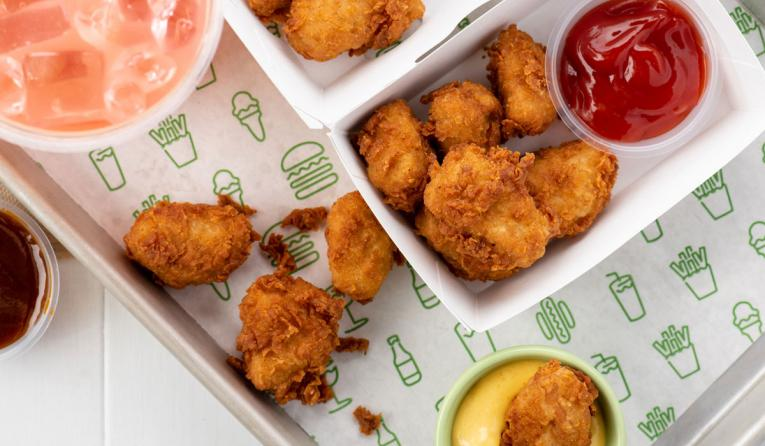 Shake Shack chicken nuggets with drinks and sauces.