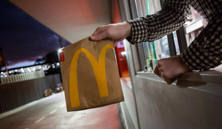 A McDonald's worker holds a bag of food out the drive thru.
