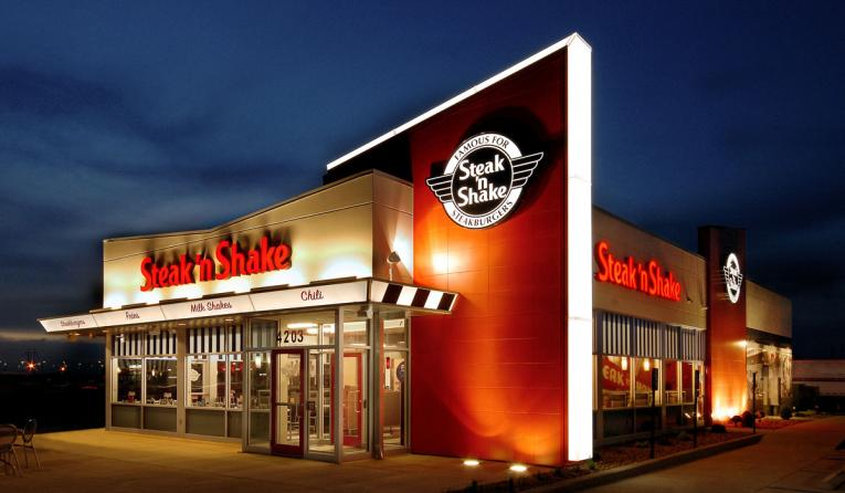 The exterior of Steak 'n Shake restaurant lit up at night.