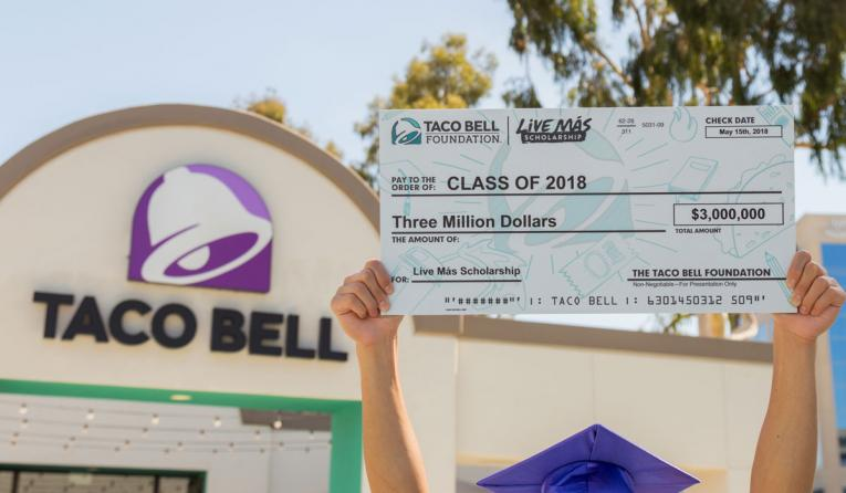 Taco Bell employee holds up a check for $3 million.