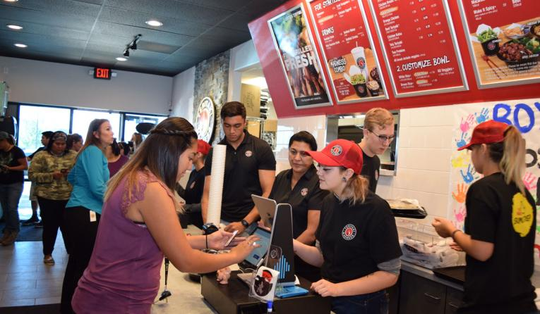 A customer orders food from a cashier at Teriyaki Madness restaurant.