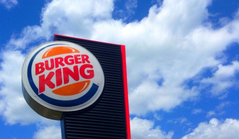 Burger King's sign showcased against a cloud-filled sky.