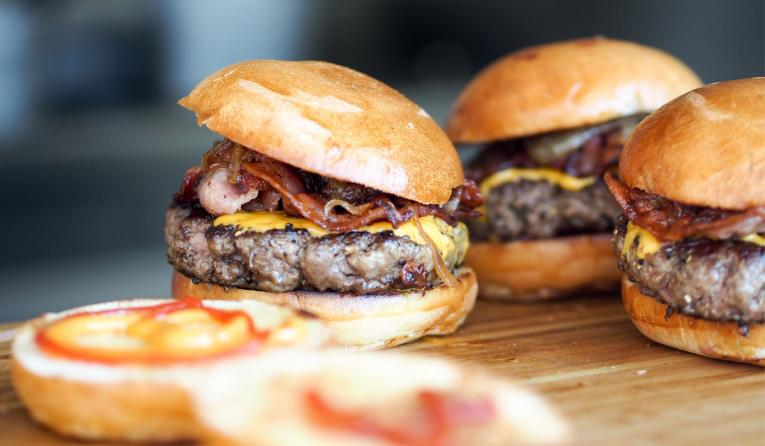 Three hamburgers with bacon on a wooden table.