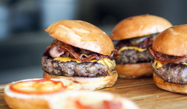 A table of burger sliders with bacon.