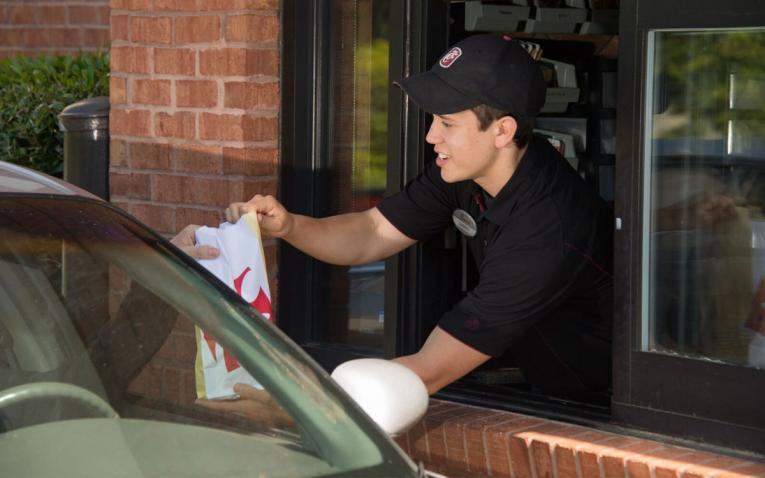 Customer gets a bag of food at Chick-fil-A in the drive thru.