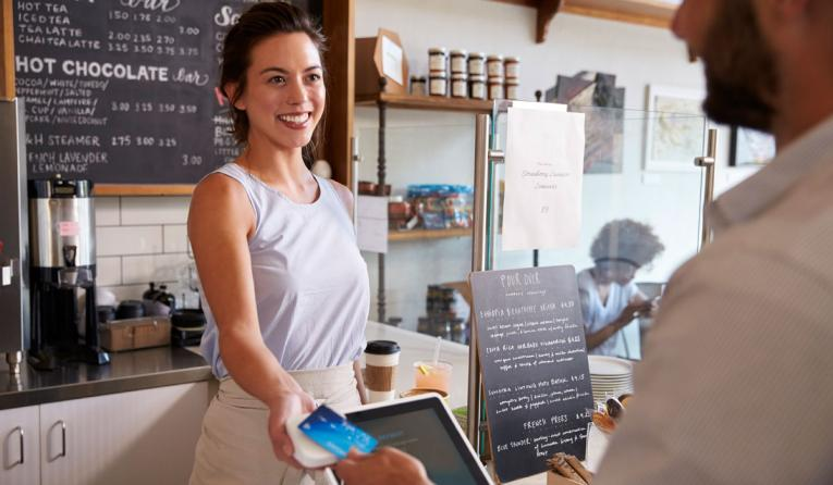 Customer at coffee shop pays smiling waitress with card.