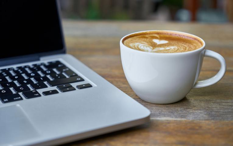 A laptop computer next to a cup of coffee on a table.
