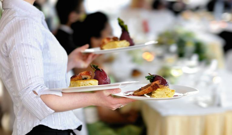 A waitress carries plates of food.