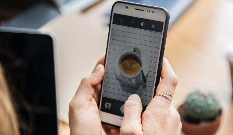 A person takes a photo of a cup of coffee with their mobile phone.