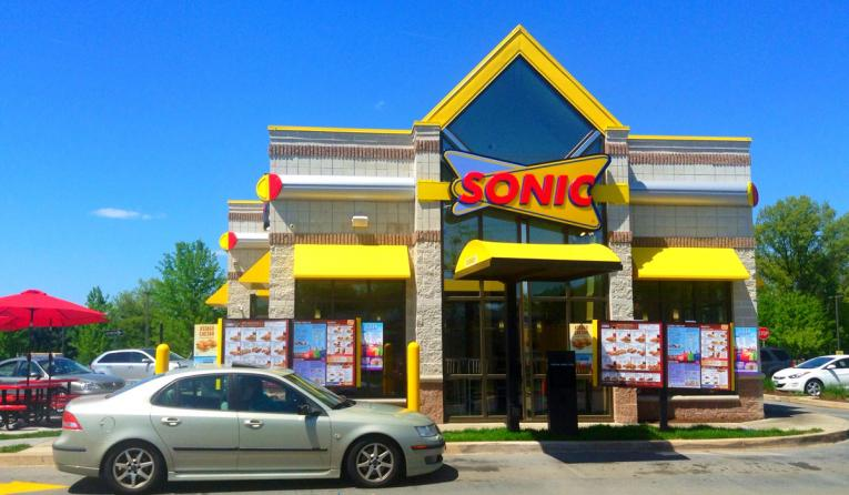 Sonic Drive-In with car parked out front.