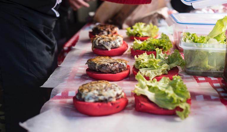 A restaurant worker makes burgers.