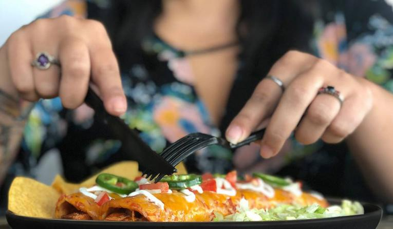 A customer cuts a burrito with a fork and knife at Tijuana Flats.